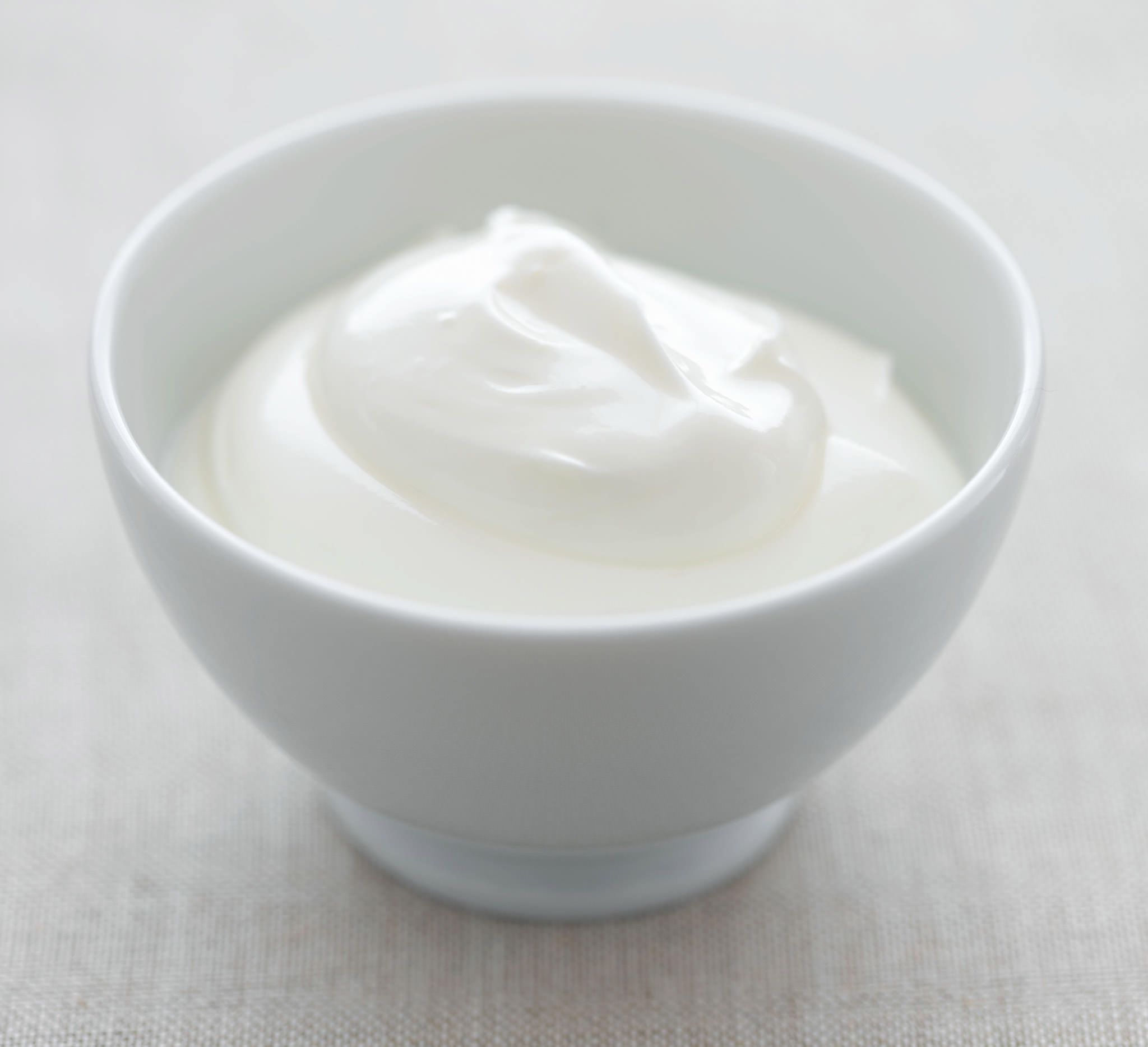 yogurt in white ceramic bowl with spoon